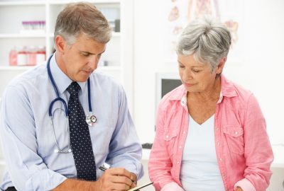 Doctor with female patient in consultation room taking notes